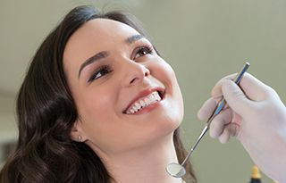 woman smiling while getting dental checkup