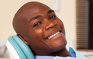 man sitting in a dental exam chair smiling